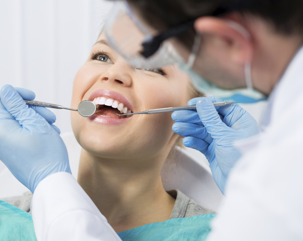Regular dentist visit. Caries cure. Young woman visiting dentist
